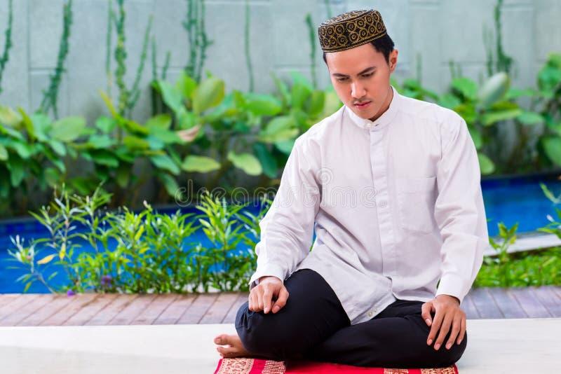 Azjatycki Muzułmański mężczyzna modlenie na dywanie fotografia royalty free