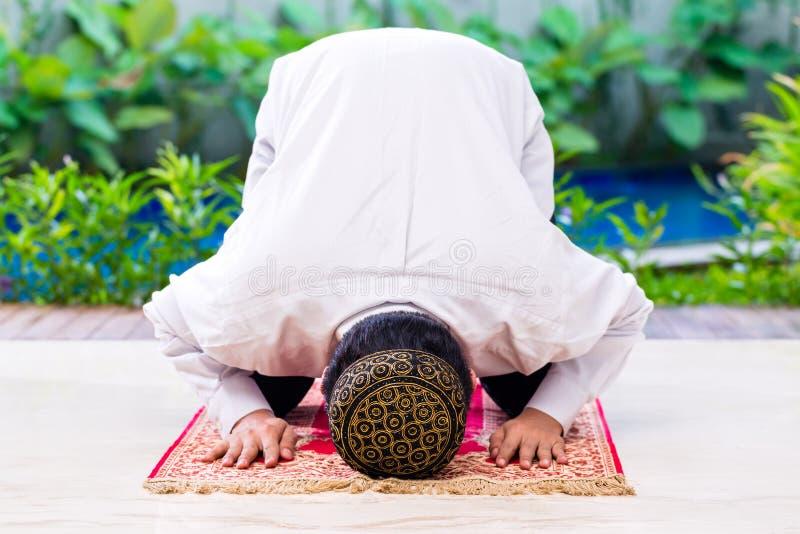 Azjatycki Muzułmański mężczyzna modlenie na dywanie zdjęcia royalty free