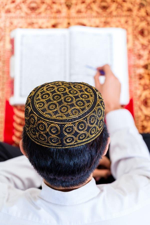 Azjatycki Muzułmański mężczyzna studiuje Koran lub koran obraz royalty free