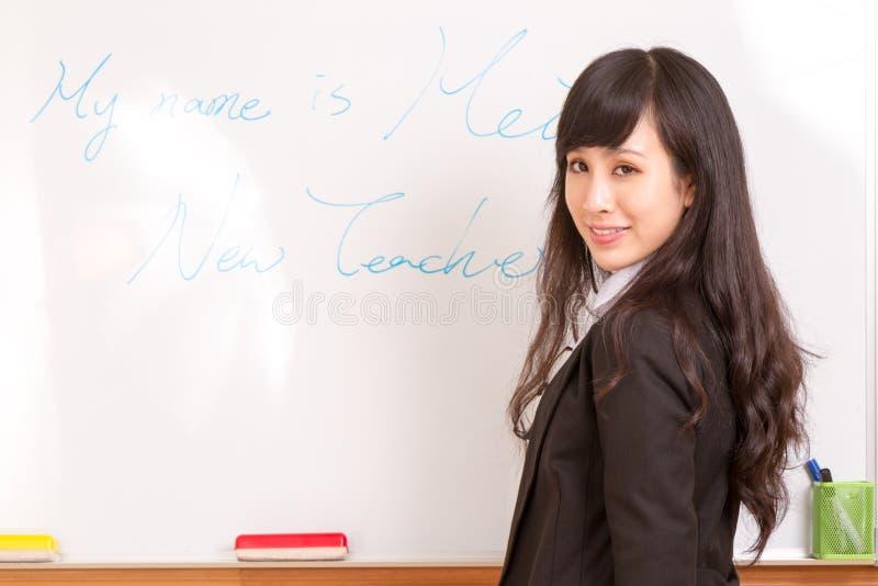 Azjatycki nauczyciela writing na whiteboard zdjęcie royalty free