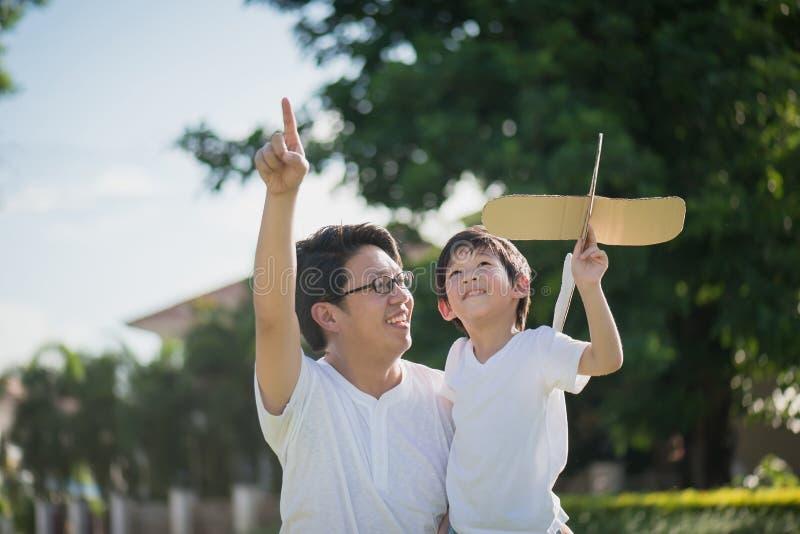 Azjatycki ojciec i syn bawić się kartonowego samolot wpólnie obraz royalty free