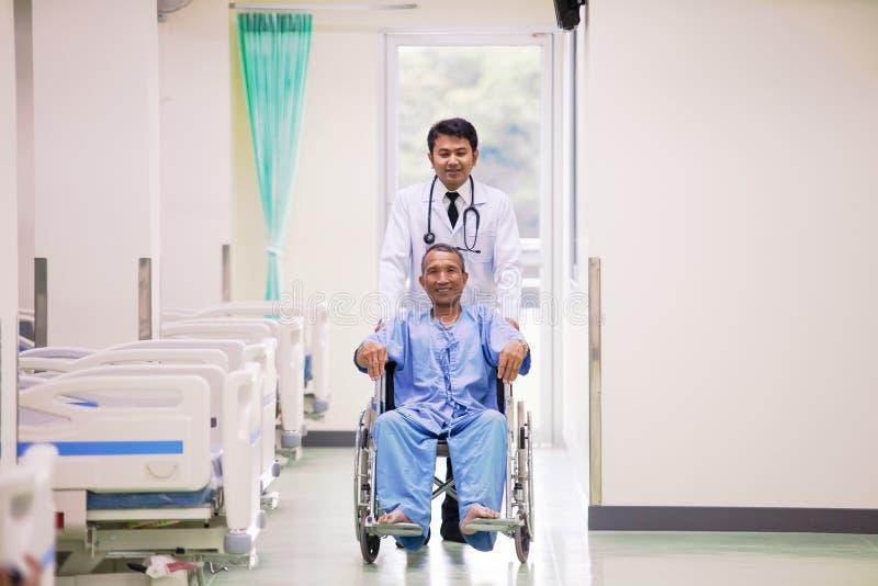Azjatycki pacjent w wózka inwalidzkiego obsiadaniu w szpitalu z Azjatyckim docto fotografia royalty free