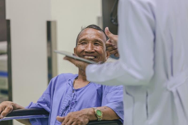 Azjatycki pacjent w wózka inwalidzkiego obsiadaniu w szpitalu z Azjatyckim docto zdjęcia royalty free