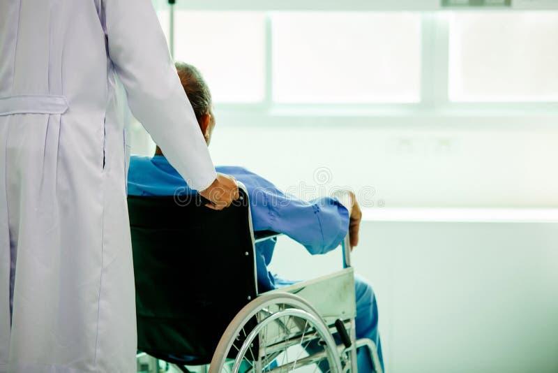 Azjatycki pacjent w wózka inwalidzkiego obsiadaniu w szpitalu z Azjatyckim docto obrazy royalty free