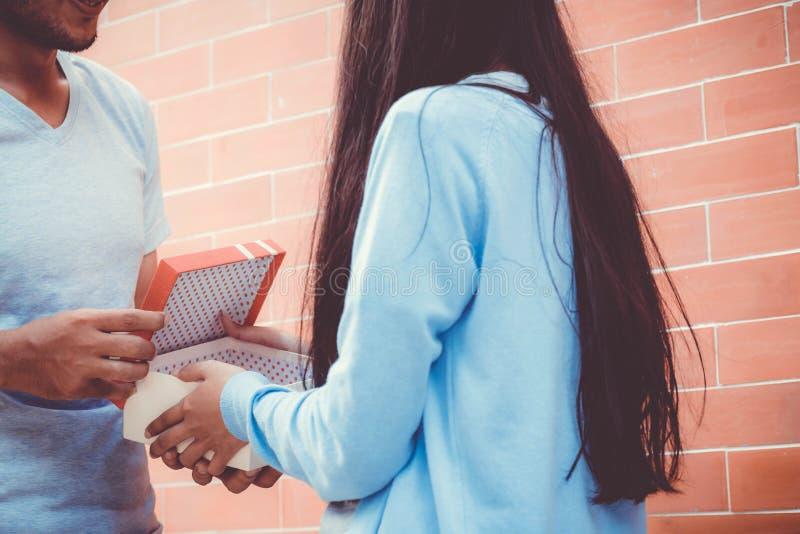 Azjatycki para młody człowiek daje prezentowi kobieta outdoors zdjęcia stock