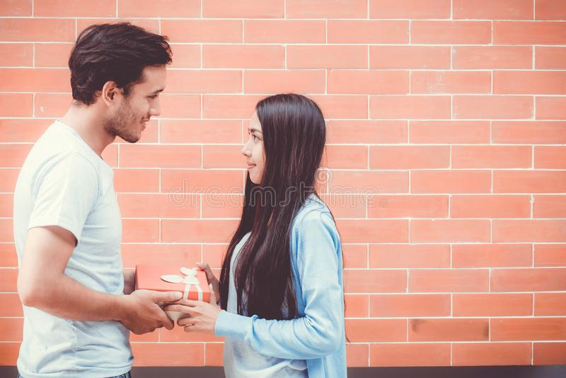 Azjatycki para młody człowiek daje prezentowi kobieta outdoors obraz stock
