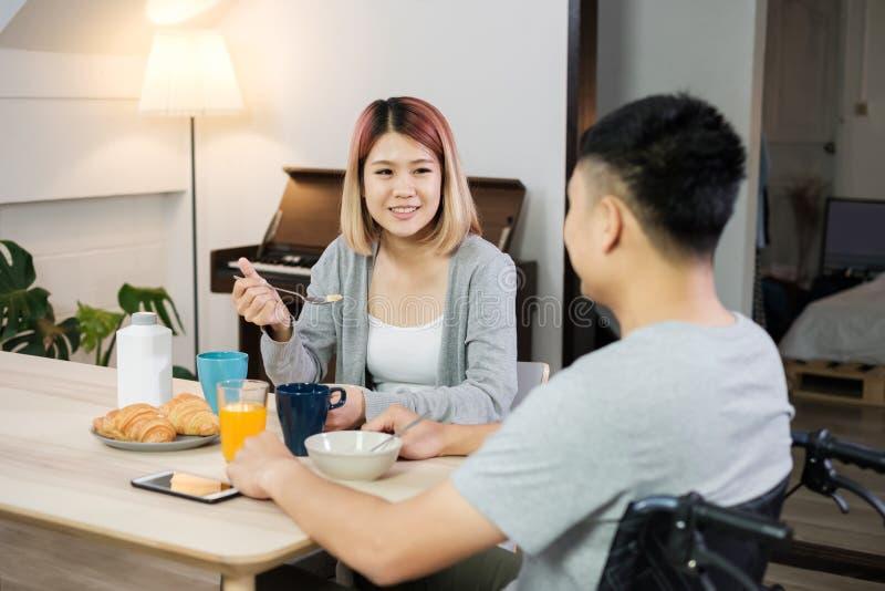 Azjatycki pary śniadanie w domu żony mienia ręka i zachęca niepełnosprawnego męża obsiadanie w wózku inwalidzkim przy kuchennym s zdjęcie royalty free