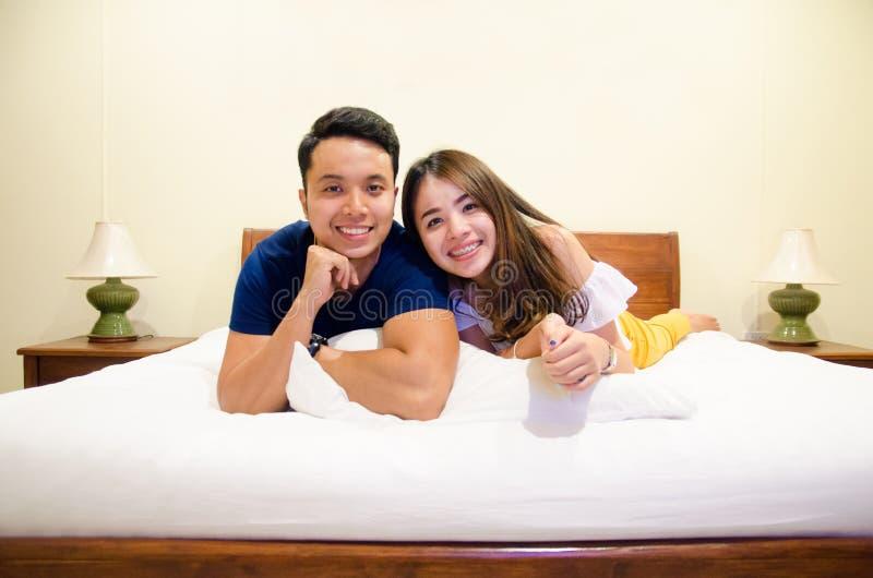 Azjatycki pary lying on the beach na łóżku fotografia royalty free