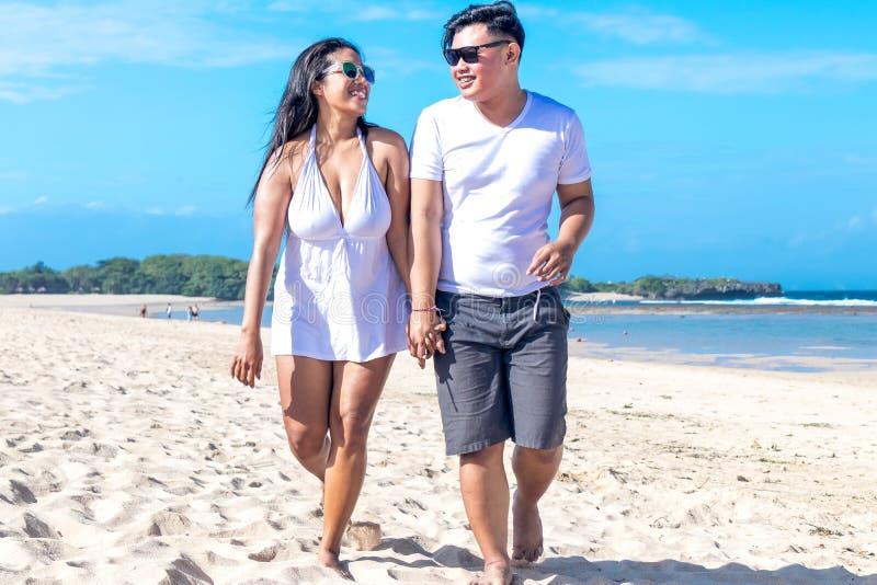 Azjatycki pary odprowadzenie na plaży tropikalna Bali wyspa, Indonezja obraz stock