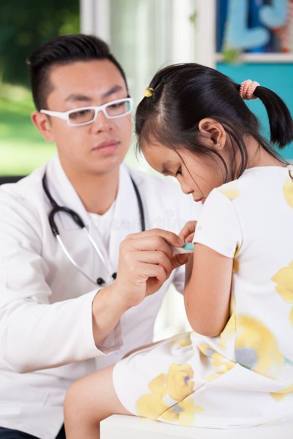 Azjatycki pediatra egzamininuje małej dziewczynki obrazy royalty free