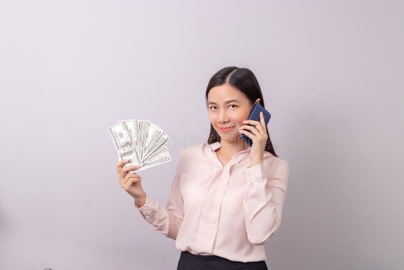 Azjatycki piękny kobiety mienia banknotu pieniądze w ręce i telefonie komórkowym w innej ręce odizolowywającej na popielatym tle obrazy royalty free