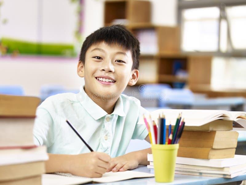 Azjatycki podstawowy uczeń robi pracie domowej w sala lekcyjnej fotografia royalty free