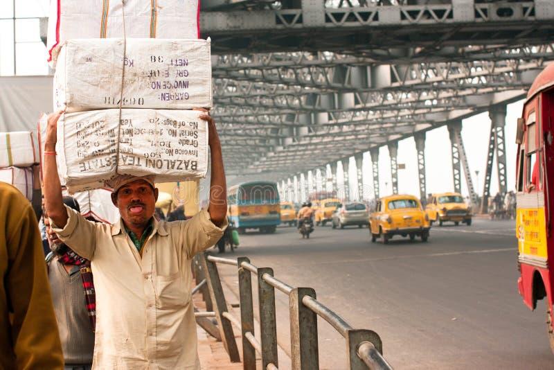 Azjatycki pracownik z ładunkiem na kierowniczym pośpiechu obraz stock