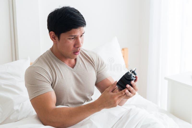 Azjatycki przystojny mężczyzna obudził budzikiem w łóżku przy ranku czasem obrazy stock