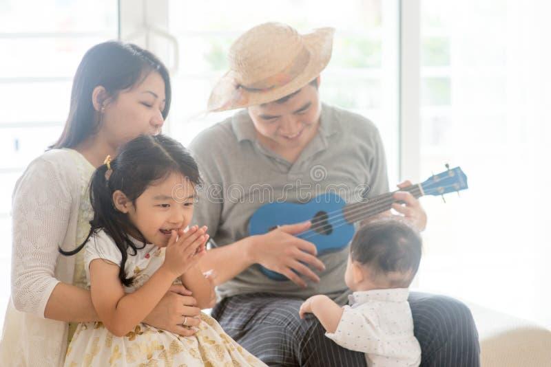 Azjatycki rodzinny bawić się ukulele obrazy royalty free