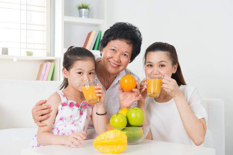 Azjatycki rodzinny pije sok pomarańczowy. fotografia royalty free
