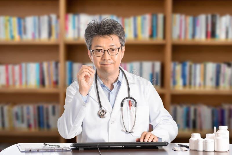 Azjatycki samiec lekarki obsiadanie przy biurka ono uśmiecha się zdjęcia stock