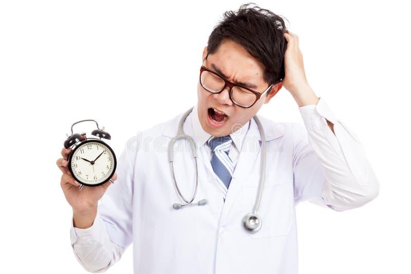 Azjatycki samiec lekarki poziewanie z zegarem fotografia stock