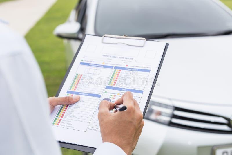 Azjatycki samochodowy technika mienia listy kontrolnej papier przed samochodem obraz stock