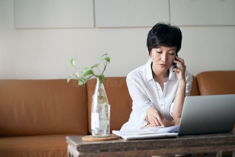 Azjatycki samozatrudniaj?cy si? kobiety obsiadanie na le?ance & dzia?anie na laptopie w domu fotografia royalty free