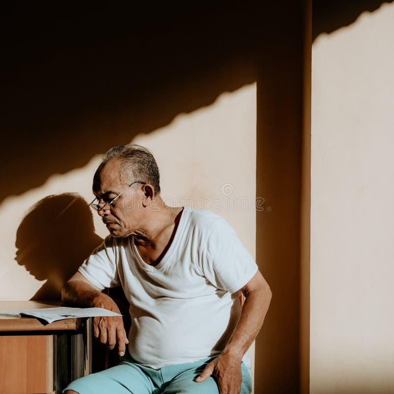 Azjatycki starego człowieka obsiadanie na krześle obraz royalty free