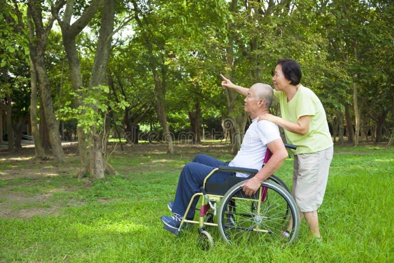 Azjatycki starszego mężczyzna obsiadanie na wózku inwalidzkim z jego żoną obraz stock