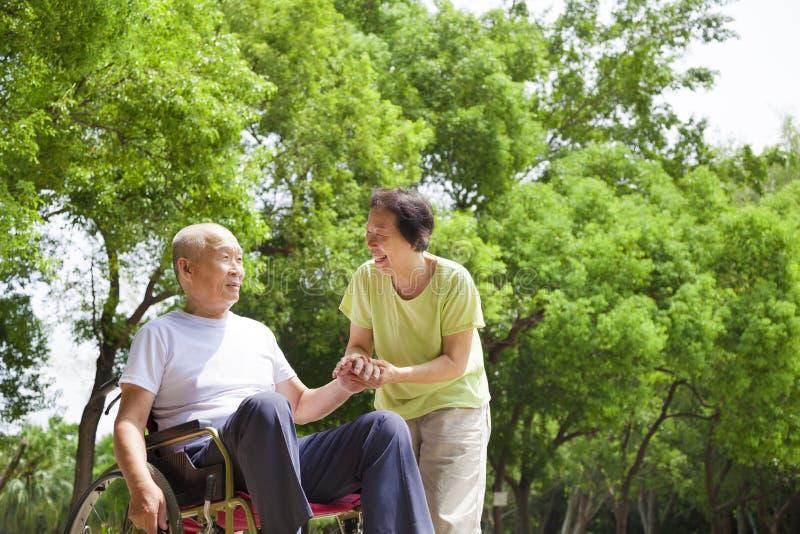 Azjatycki starszego mężczyzna obsiadanie na wózku inwalidzkim z jego żoną obrazy royalty free
