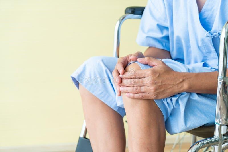 Azjatycki starszy cierpliwy wózek inwalidzki z kolano bólem obraz royalty free