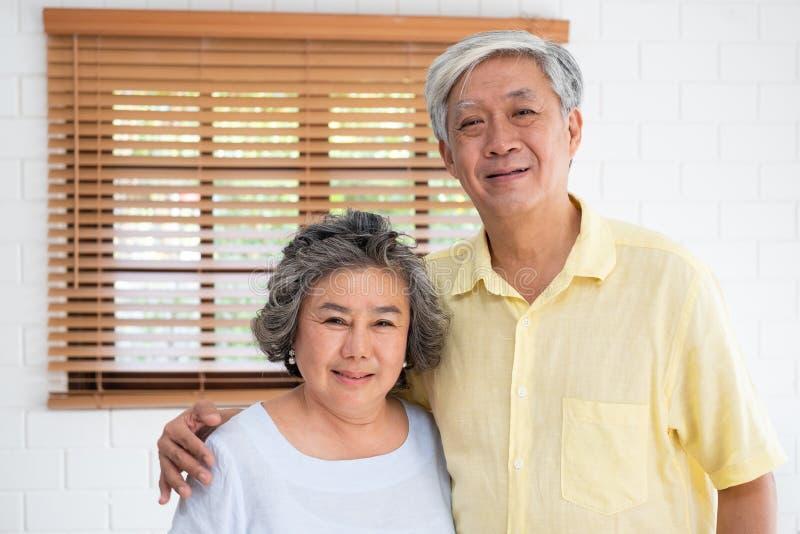 Azjatycki starszy para uścisku togerther i patrzeć kamerę w żywym pokoju w domu Szczęśliwy emerytury lfie starzeć się w domu poję obrazy stock