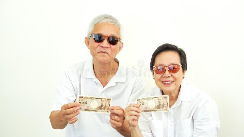 Azjatycki starszy pary mienia gotówki japońskiego jenu pieniądze fotografia stock