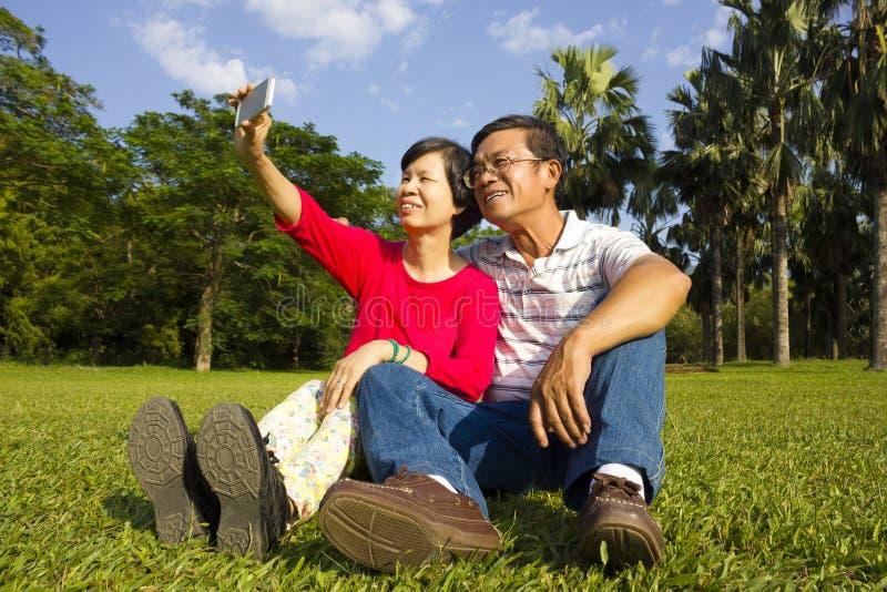 Azjatycki Starszy pary obsiadanie na obszarze trawiastym i brać obrazku obrazy royalty free