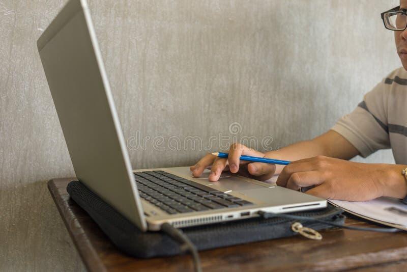 Azjatycki studencki mienia pióro podczas gdy używać laptop obrazy stock