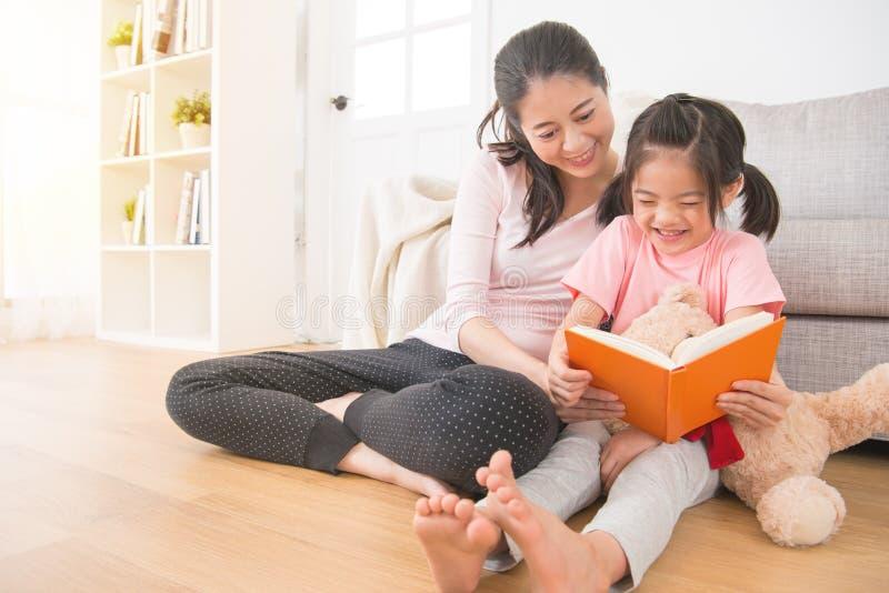 Azjatycki szczęśliwy dziewczyny mienia miś ogląda komiczkę zdjęcia royalty free