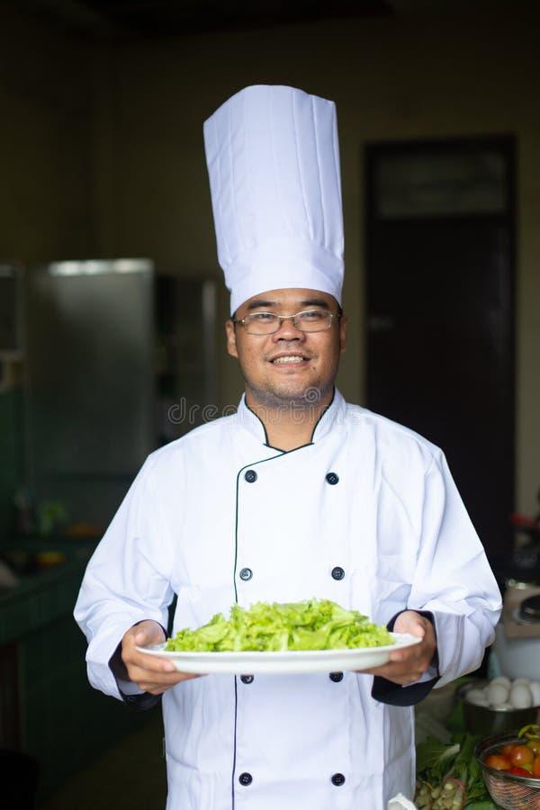 Azjatycki szef kuchni w kuchni z zdrowym jedzeniem obraz royalty free