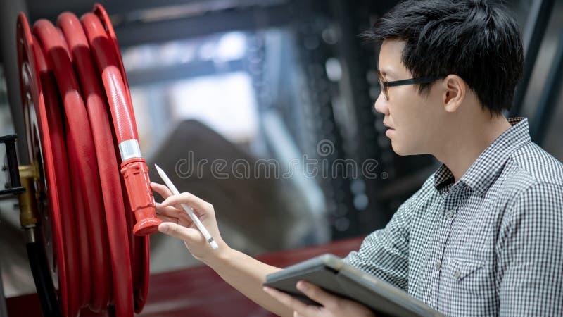 Azjatycki technik sprawdza pożarniczego węża elastycznego rolkę fotografia stock