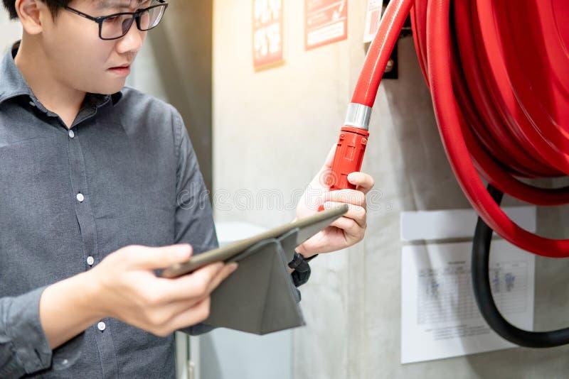 Azjatycki technik sprawdza po?arniczego w??a elastycznego rolk? fotografia royalty free