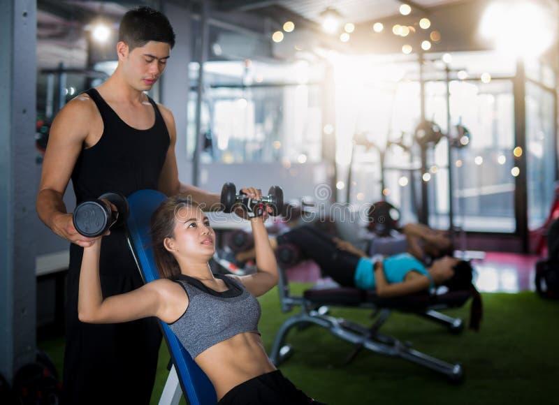 Azjatycki trener i dama bierzemy osobistego szkolenie w sprawność fizyczna klubie zdjęcie stock