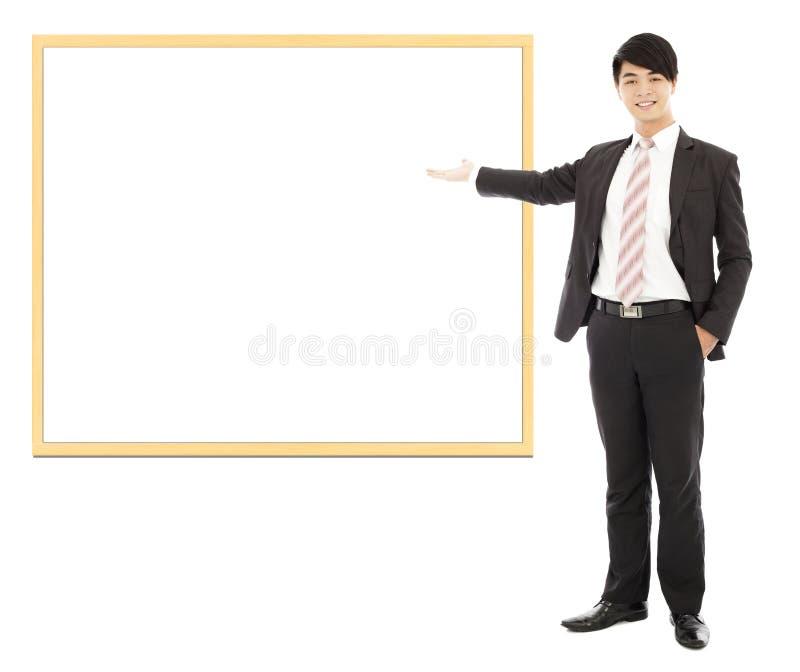 Azjatycki uśmiechnięty biznesowy mężczyzna wskazuje puste miejsce deskę zdjęcia stock