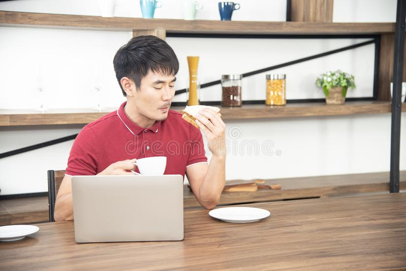 Azjatycki uśmiechnięty młody człowiek z przypadkową czerwoną koszulką cieszy się mieć śniadanie, młodego człowieka kulinarnego je zdjęcie royalty free