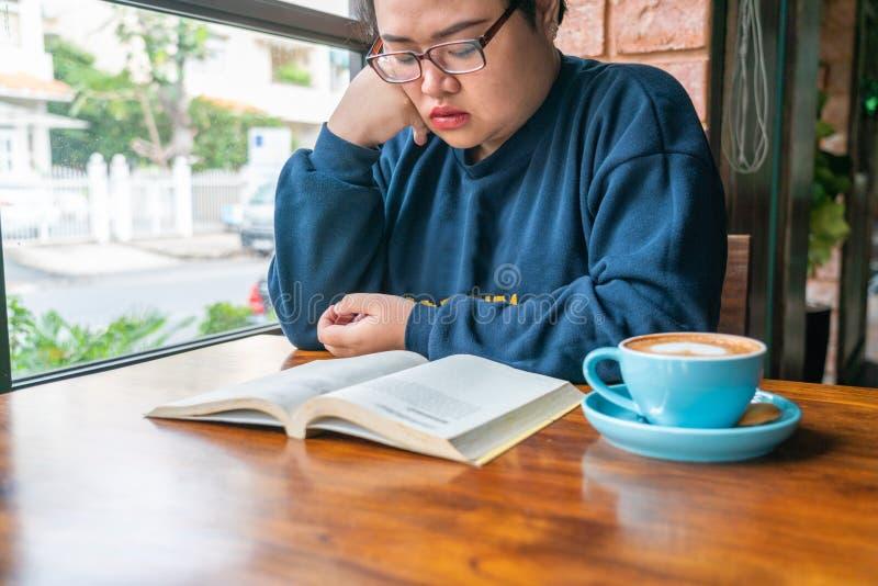 Azjatycki uczeń cieszy się dzień z książką i kawą zdjęcie royalty free