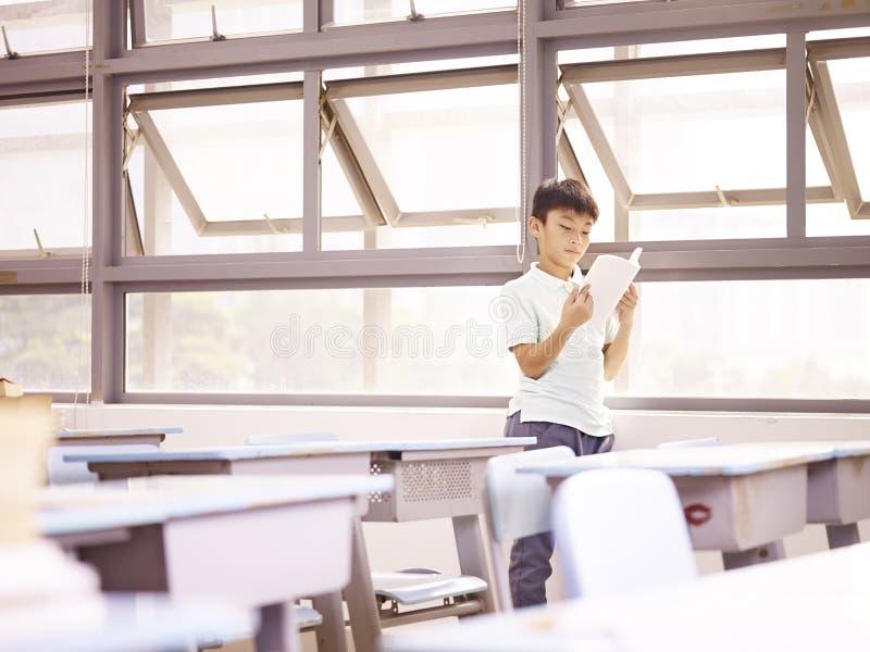 Azjatycki uczeń czyta książkę okno zdjęcie stock