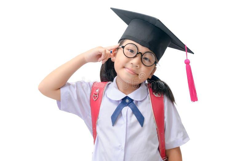 Azjatycki uczeń jest ubranym magisterską nakrętkę i główkowanie obraz royalty free