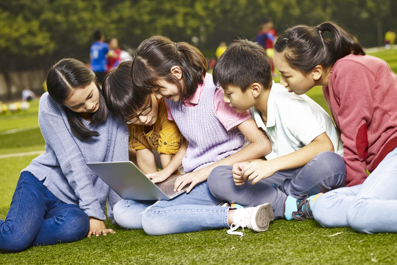 Azjatycki uczeń używa laptop outdoors obraz stock