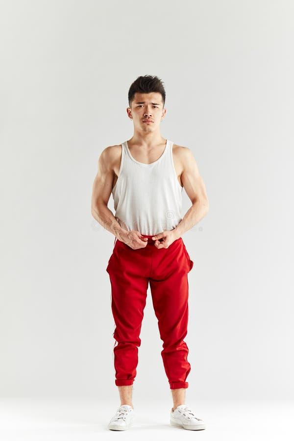 Azjatycki uliczny tancerz w czerwieni dyszy rozgrzewkowego w g?r? treningu w bia?ym studiu przed fotografia royalty free