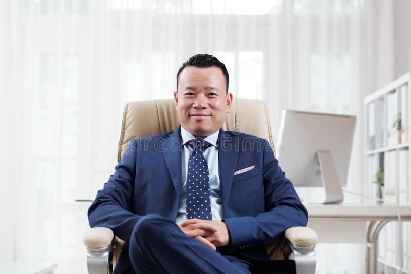 Azjatycki wykonawczy obsiadanie przy biurem obrazy royalty free