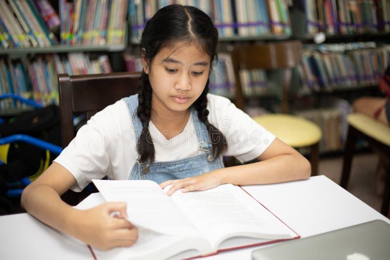 Azjatyckich uczni czytelnicze książki w bibliotece obraz royalty free