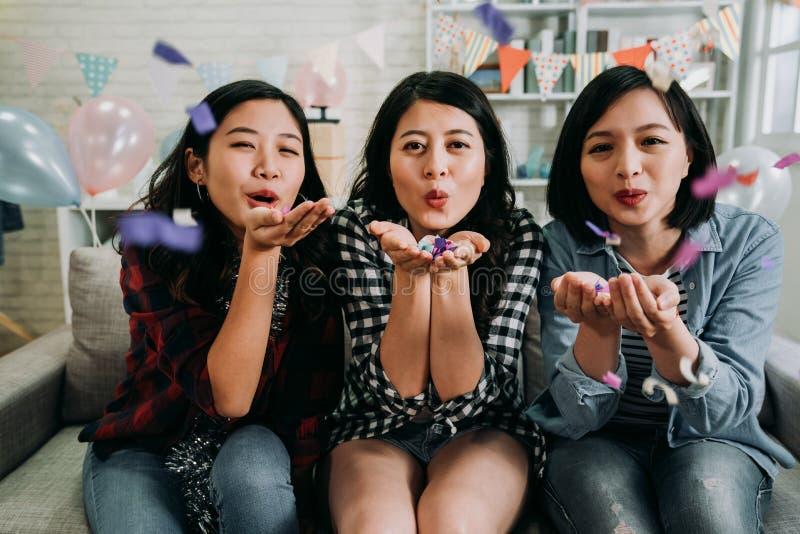 Azjatyckie śliczne damy dmucha kolorowych confetti zdjęcie royalty free