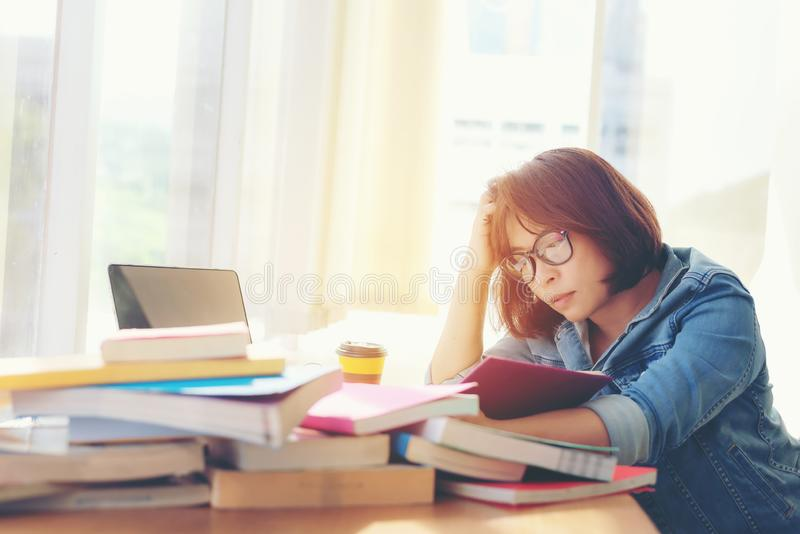 Azjatyckie azjatykcie kobiety czyta coś w książce i bierze notatki przy szkoły wyższej biblioteką zdjęcie stock