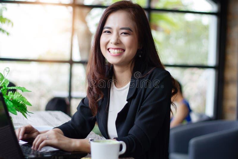 Azjatyckie biznesowe kobiety uśmiecha się notatnika i używa dla pracować przy kawową kawiarnią obrazy stock