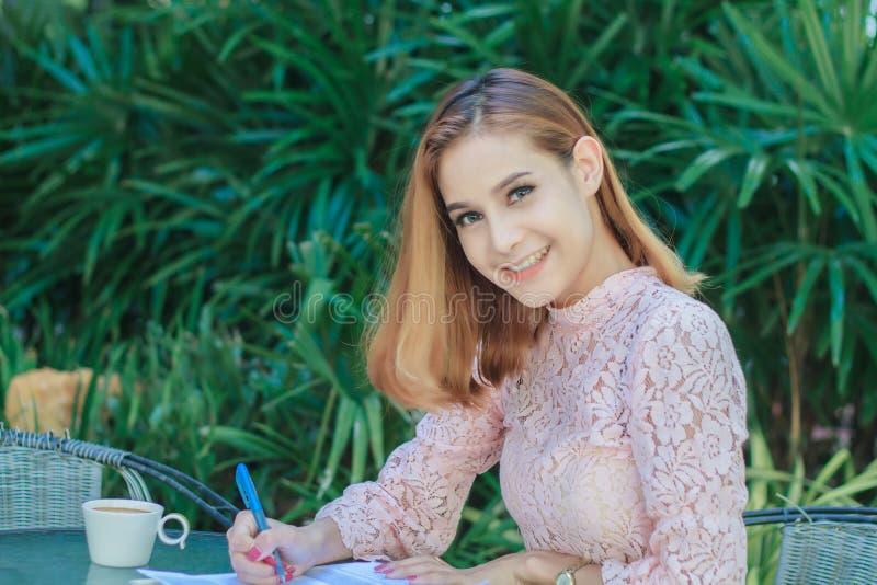 Azjatyckie biznesowe kobiety uśmiecha się pracować che i pisać książce i fotografia royalty free